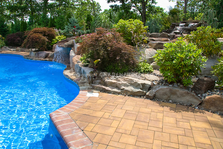 Swimming pool landscaping with deck patio, shrubs, trees, perennial plants, raised beds around rocky sloped hillside, waterfalls incorporated into problem site