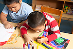 Education prechool 3-4 year olds two boys sitting side by side art activity drawing with colored makers