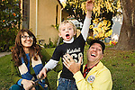 Mother and father laugh holding onto their blonde pre-school son as he lunges forward on grassy slope outdoors in front of house.