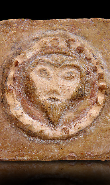Detail of a 6th-7th Century Eastern Roman Byzantine  Christian Terracotta tiles depicting Christ - Produced in Byzacena -  present day Tunisia. <br /> <br /> These early Christian terracotta tiles were mass produced thanks to moulds. Their quadrangular, square or rectangular shape as well as the standardised sizes in use in the different regions were determined by their architectonic function and were designed to facilitate their assembly according to various combinations to decorate large flat surfaces of walls or ceilings. <br /> <br /> Byzacena stood out for its use of biblical and hagiographic themes and a richer variety of animals, birds and roses. Some deer and lions were obviously inspired from Zeugitana prototypes attesting to the pre-existence of this province's production with respect to that of Byzacena. The rules governing this art are similar to those that applied to late Roman and Christian art with, in the case of Byzacena, an obvious popular connotation. Its distinguishing features are flatness, a predilection for symmetrical compositions, frontal and lateral representations, the absence of tridimensional attitudes and the naivety of some details (large eyes, pointed chins). Mass production enabled this type of decoration to be widely used at little cost and it played a role as ideograms and for teaching catechism through pictures. Painting, now often faded, enhanced motifs in relief or enriched them with additional details to break their repetitive monotony.<br /> <br /> The Bardo National Museum Tunis, Tunisia.  Against a black background.