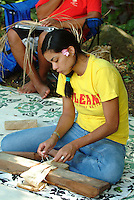A Hawaiian girl works on a pounding board to soften a piece of tapa (kapa) cloth made from bark. Kapa was used for clothing, bedding, and other materials.