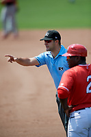 Umpire Thomas Fornarola points to the Lowell Spinners bench to give a warning as Batavia Muckdogs coach Ronnie Richardson (2) looks on during a game on July 15, 2018 at Dwyer Stadium in Batavia, New York.  Lowell defeated Batavia 6-2.  (Mike Janes/Four Seam Images)