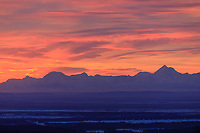 The winter sunrise lights the clouds over the Alaska Range mountains behind the city of Fairbanks. Mt. Hayes on the right.
