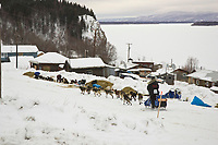 Rick Casillo runs down the street as he leaves Ruby on Saturday morning with the Yukon River in the background during Iditarod 2008