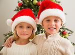 Brother (6-7) and sister (6-7) wearing Santa hats