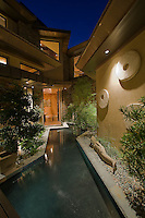 Water feature is shown at night in front courtyard of modern home