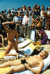 Cannes Film Festival semi nude woman topless on beach boyfriend pose for amateur and press photographers at work working. 1980s France