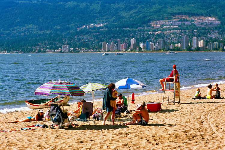 People sunbathing at Third Beach, Stanley Park at English Bay, Vancouver, BC, British Columbia, Canada, Summer - West Vancouver in background