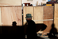 .Old man walking early morning in the 16 de Julio Street Fair.Just 25 years ago it was a small group of houses around La Paz  airport, at an altitude of 12,000 feet. Now El Alto city  has  nearly one million people, surpassing even the capital of Bolivia, and it is the city of Latin America that grew faster .<br /> It is also a paradigmatic city of the troubles  and traumas of the country. There got refugee thousands of miners that lost  their jobs in 90 ´s after the privatization and closure of many mines. The peasants expelled by the lack of land or low prices for their production. Also many who did not want to live in regions where coca  growers and the Army  faced with violence.<br /> In short, anyone who did not have anything at all and was looking for a place to survive ended up in El Alto.<br /> Today is an amazing city. Not only for its size. Also by showing how its inhabitants,the poorest of the poor in one of the poorest countries in Latin America, managed to get into society, to get some economic development, to replace their firs  cardboard houses with  new ones made with bricks ,  to trace its streets,  to raise their clubs, churches and schools for their children.<br /> Better or worse, some have managed to become a sort of middle class, a section of the society that sociologists call  emerging sectors. Many, maybe  most of them, remain for statistics as  poor. But clearly  all of them have the feeling they got  for their children a better life than the one they had to face themselves .