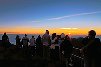 Male and female tourists enjoy the sunrise atop the Haleakala crater on Maui in Hawaii USA