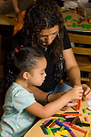 Preschool transition to start of school parent mother staying in classroom at beginning of day doing activity with daughter helping her stack small blocks