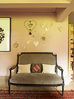 A Louis XVI canape against a wall in the living room on which is displayed a collection of hearts