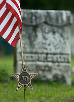 A 1776 military marker and flag fly at the gravestone of a man buried in the cemetery at St. Josephs Church in Somerset, Ohio. The church is the oldest Catholic church in Ohio...<br />