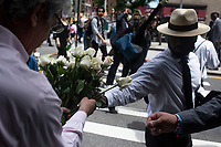 NEW YORK, NEW YORK - JUNE 04: Detail of supporter giving flowers in  march against the death of George Floyd and hold the funeral on June 4, 2020 in Harlem, New York. The white police officer, Derek Chauvin, has been charged with second-degree murder and further charges are pending for the three other officers who participated in the arrest. Floyd's death, the most recent in a series of deaths of black Americans at the hands of the police, has set off days and nights of protests across the country. (Photo by Joana Toro / VIEWpress via Getty Images)