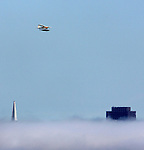 A seaplane flies over the tallest buildings in San Francisco while the fog blankets the bay area.