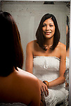 Young Hispanic woman looking at her reflection in the mirror