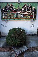 Switzerland. Canton Ticino. Brè. Cemetery with tombstones. On the wall, a mosaic by Wilhelm Schmid of joyful men celebrating the last supper. Wilhelm Schmid (1892–1971) was a Swiss painter, who focuses on New Objectivity and Magic Realism. The Last Supper represents the scene of the Last Supper of Jesus with his apostles, as it is told in the Gospel of John. A mosaic is a piece of art or image made from the assembling of small pieces of colored glass, stone, or other materials. It is often used in decorative art. Most mosaics are made of small, flat, roughly square, pieces of stone or glass of different colors, known as tesserae. The village of Brè lies on the eastern slope of Monte Brè. 23.03.2019 © 2019 Didier Ruef