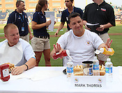 """Mark Thomas prepares his hotdogs with ketchup and mustard during the Bright Leaf Hotdog Eating Conest on Sunday, July , 2011. """"I've been training for this all my life,"""" said Thomas. Photo by Al Drago."""