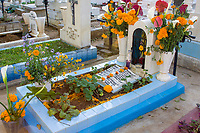 Oaxaca; Mexico; North America.  Day of the Dead Celebration.  Grave Decorated with Marigolds, the traditional flower used for this occasion.