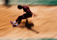 Blurred action image of a male athlete doing the long jump at a track meet.
