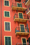 Balconies and window shutters - all of them closed - nearby the beach of Camogli. Warm colors of the wall contrasting cold colors of the window shutters and handrails.
