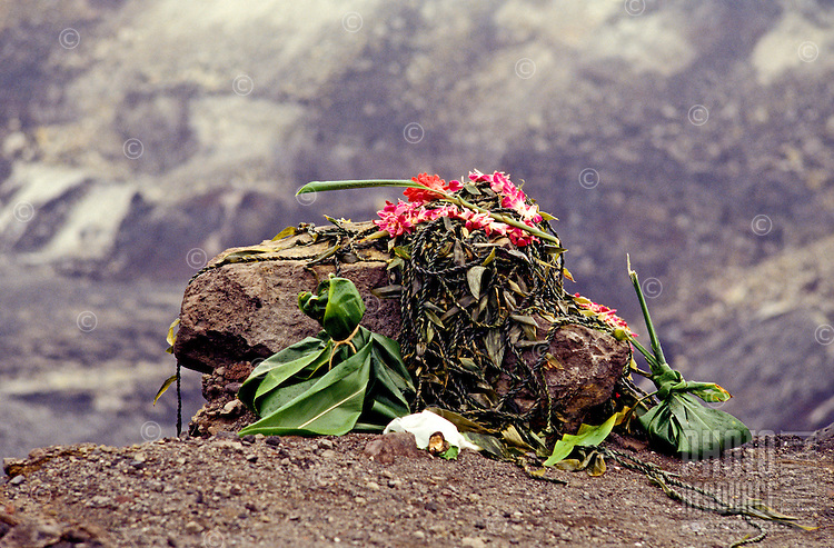 An offering to the Hawaiian Fire Goddess Pele consisting of braided ti leaves, flower lei and traditional ho`okupu (ti leaf bundles) is left on a rock in Halemaumau Crater, Volcanoes National Park on the Big Island of Hawaii.