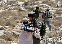 """An Israeli soldier fires tear gas toward Palestinian protestors during a demonstration against the construction of Israel's controversial separation barrier in the West Bank village of Nilin, west of Ramallah on May 25, 2008. """"photo by Iyad Jadallah"""""""