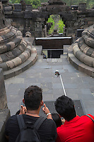 Borobudur, Java, Indonesia.  Four Young Indonesians Using an Extension Pole to Take a Selfie while Visiting the Temple.