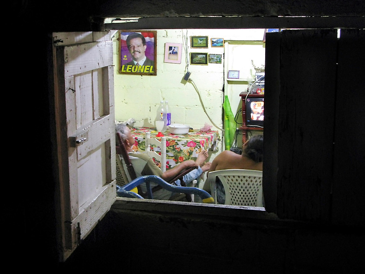 Couple watches television in their home, Rio San Juan, Dominican Republic
