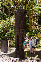 "Tourists read a sign next to a carved wooden tiki (or ki'i in Hawaiian, or statue) of the Hawaiian god ""KU"" at Hawaii Tropical Botanical Garden, Papa'ikou (near Hilo), Big Island of Hawaiʻi."