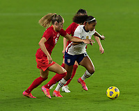 ORLANDO CITY, FL - FEBRUARY 18: Margaret Purce #20 splits two opponents during a game between Canada and USWNT at Exploria stadium on February 18, 2021 in Orlando City, Florida.