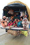 A group of pilgrims squeeze themselves, their luggage, and camping equipment into the back of a truck for the journey back home after attending the Maha Kumb Mela 2013.