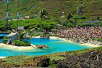 Wide angle shot at Sea Life Park on Oahu highlighting water show facilities and lined with hundreds of tourists.