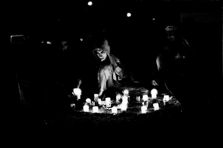 Woman lighting candles outside the gates of the Muqata presidential compound the night before Yasser Arafat's funeral.