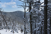 Hiker ascending the Hancock Loop Trail in the White Mountains, New Hampshire during the winter months. This trail travels to Mount Hancock which is named after John Hancock, one of the Founding Fathers of the United States.