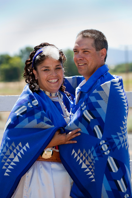 Newly wed couple dressed in traditional clothing are wrapped together inside an Indian blanket as a symbol of a long and happy marriage.