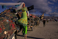 Wind blows the veil of a green dressed man on stilts at the annual, weeklong Burning Man Festival held at Black Rock Playa in northwestern Nevada's Conservation area.  The annual weeklong festival celebrates art in the backdrop of the vast playa, one of Earth's flattest spots. Over 26,000 people create an instant city embracing a unique counter-cultre experience.