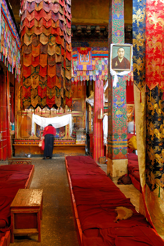 Buddhist pilgrim prays in the main hall of Ramoche Temple, amid silk embroidered adorned columns, built in the 7th century, sister to the Jokhang Temple, Lhasa, Tibet, China.