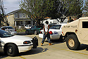 A criminal suspect waits to be booked after being arrested by New Orleans police shadowed by Louisiana National guardsmen in the  Ninth Ward, New Orleans, Thurs., June 22, 2006.