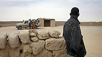 A migrant looks on in Khalil, a settlement on the border between Mali and Algeria, in the middle of the desert, as a car prepares to transport migrants across the border.