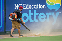 Kannapolis Intimidators assistant grounds keeper Erik Salmon uses a leaf blower to remove water from the warning track prior to the game against the West Virginia Power at Kannapolis Intimidators Stadium on June 17, 2017 in Kannapolis, North Carolina.  The Power defeated the Intimidators 6-1.  (Brian Westerholt/Four Seam Images)