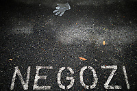 Switzerland. Canton Ticino. Lugano. Winter season. A plastic glove on the sidewalk. The glove was used to protect a person against the coronavirus (also called Covid-19). On the pavement, a parking place reserved for the shops (negozi). 21.12.2020 © 2020 Didier Ruef