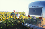 Couple standing in a field of sunflowers next to their vintage Airstream travel trailer.