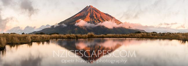 Sunset over Taranaki, Mt. Egmont with reflections in alpine tarn, Egmont National Park, North Island, New Zealand, NZ