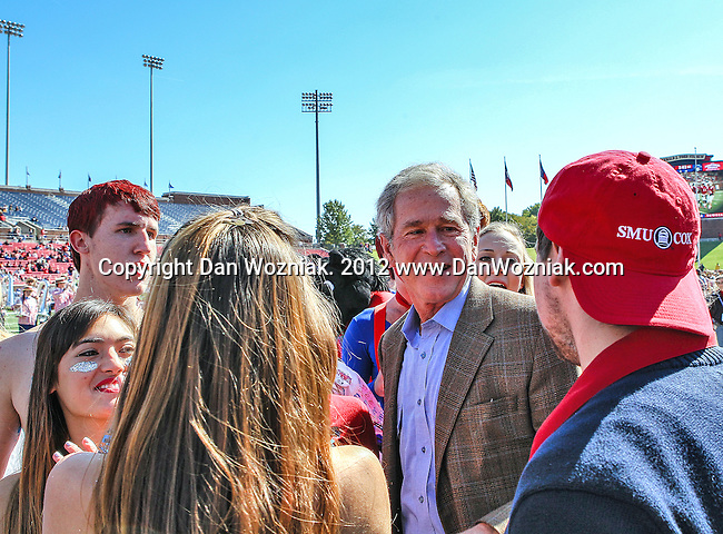 Former President George W. Bush participates in the pre game coin toss before the game between the Memphis Tigers and the Southern Methodist Mustangs at the Gerald J. Ford Stadium in Dallas, Texas. SMU defeats Memphis 44 to 13.
