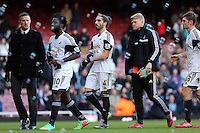 Pictured: Chico Flores of Swansea (C) walking off the pitch with team mates Wilfried Bony (2nd L) David Cornell (4th L) and Ben Davies (R). 01 February 2014<br />