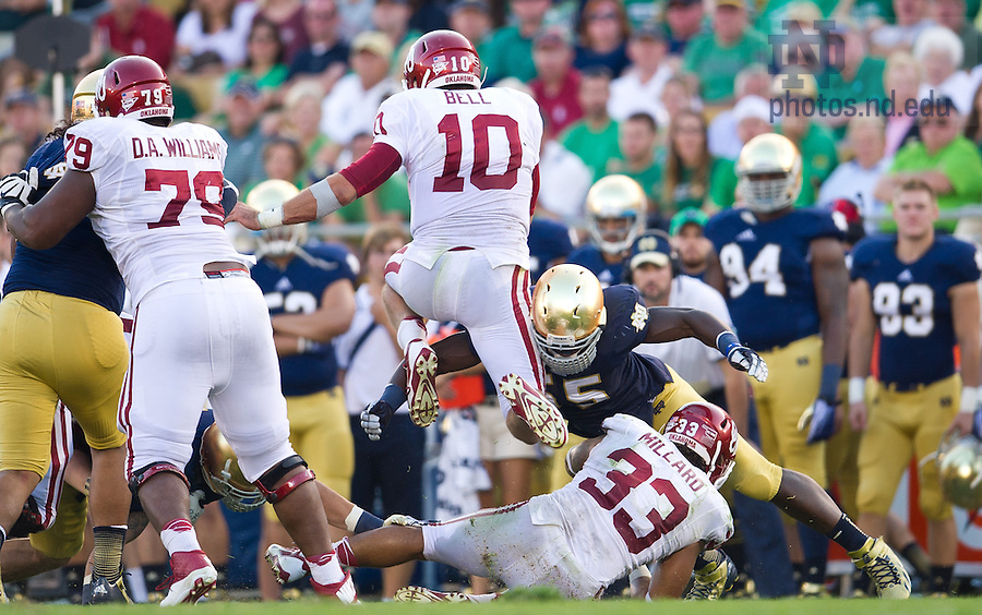 Sept. 28, 2013; Oklahoma QB Blake Bell (10) carries the ball as Notre Dame Fighting Irish linebacker Prince Shembo (55) attempts to tackle in the fourth quarter.<br /> <br /> Photo by Matt Cashore