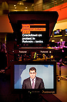 Newsreader Sami Zeidan broadcasts in the newsroom for news channel Al Jazeera English in Doha. The autocue shows what he is reading.