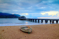 Twilight at Hanalei Bay, Kauai, with a small boat on the sand and the pier in the background.