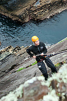 Clare Island, Ireland, July 2013. abseiling an climbing  along the irish coastline on Clare Island.  It is the first time that Tallship Thalassa, a barquentine sailing vessel with 3 masts, sails from Belfast to Galway along the Irish coastline. While a full-rigged ship is square-rigged on all three masts, and the barque is square-rigged on the foremast and main, the barquentine extends the principle by making only the foremast square-rigged. The advantages of a smaller crew, good performance before the wind and the ability to sail relatively close to the wind while carrying plenty of cargo made it a popular rig at the end of the 19th century. Photo by Frits Meyst/Adventure4ver.com